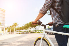 Walking with bicycle. Cropped image of man with bicycle walking in the street Royalty Free Stock Images