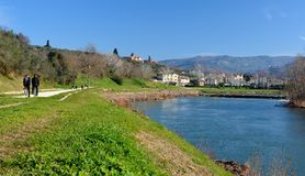 Walking on a bicycle. Cycling on Sunday mornings on the bank of the Arno nin Florence there are many cycle path of the river Arno people jog and walk Royalty Free Stock Photo