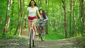Walking on bicycles in the green forest two girls climb the path to the hill , sunny day. Telephoto shot stock video