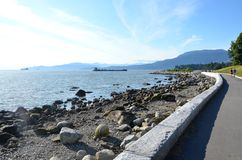 Walking and biking trail by the ocean in Vancouver. A nature trail along the rocky beach and ocean in Vancouver, British Columbia, Canada. This paved sidewalk Royalty Free Stock Photo