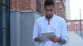 Walking Black Man and Using Tablet for Browsing. Creative designer , businessman stock footage