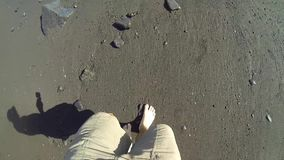 Walking on a black sand beach stock footage