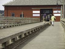 Walking the Boardwalk. A man and woman walking their dog on a wooden walkway toward red wooden building on bayside Stock Image