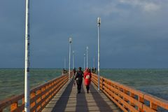 Wooden boardwalk to the sea in cloudy day royalty free stock photography