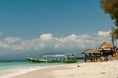 Walking boat moored to sandy beach. With beach gazebo Stock Images