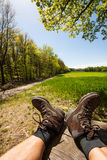 Walking boots. Relaxing hiker with lifted hiking boots and view to a meadow in front of the forest, Odenwald, Germany, Europe Royalty Free Stock Photo