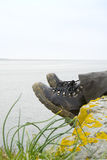 Walking boots with sea in background Stock Photo
