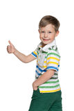 Walking boy holds his thumb up Stock Images