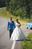 Walking Bride and Groom. Couple walking on road with bouquet Stock Image