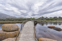 Walking bridge across a river. A small wooden and iron walking bridge going over a calm river towards a far shore with a tree line and a mountain range to a side Royalty Free Stock Photo