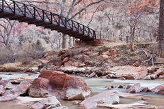 Walking bridge over calm river with red rocks. Gorgeous soft water shot of the Virgin River with a wooden bridge in Zion's National Park Stock Photos