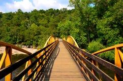 Walking bridge over river in the woods Stock Photos