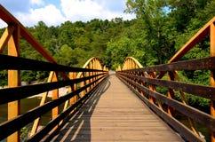 Walking bridge over river in the woods Stock Image