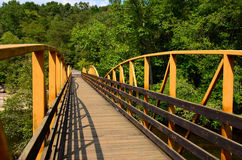 Walking bridge over river in the woods Royalty Free Stock Photo