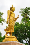 Walking Buddha. Golden walking Buddha image with clear white sky and trees in background Royalty Free Stock Photos