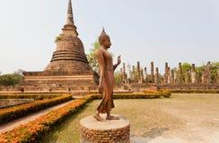 Walking Buddha statue past Buddhist stupa Stock Image