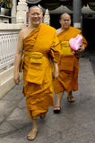 Walking buddhist monks. Picture of buddhist monks in their orange attire after doing some shopping Royalty Free Stock Image