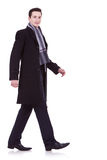 Walking business man. Side view of a walking business man, looking to the camera, on white background Stock Image