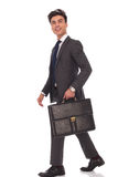 Walking business man with briefcase looking up and laughing Royalty Free Stock Images