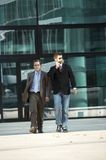 Walking business men. Young business men walking away from there office building Stock Photo