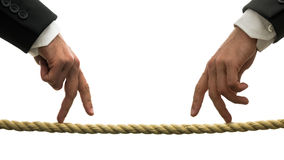 Walking a business tightrope. Conceptual image of walking a business tightrope with the hands of two businessmen walking their fingers along a rope from opposite Stock Photos