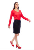 Walking business woman in red. Woman wearing red walking looking cheerful isolated on white Royalty Free Stock Images