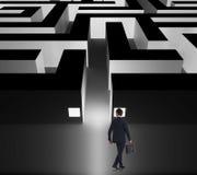 Walking businessman deciding whether to enter the business maze Stock Photo