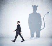 Walking businessman with devil shadow