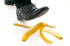 Walking businessman is going to slip on banana peel Stock Images