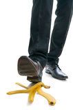 Walking businessman is going to slip on banana peel Royalty Free Stock Images