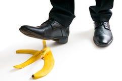 Walking businessman is going to slip on banana peel Stock Image