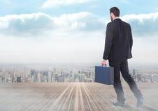 Walking businessman over city. Digital composite of Walking businessman over city Royalty Free Stock Images