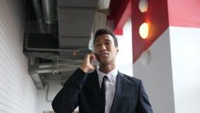 Walking Businessman Talking on Phone in Office, Happy Mood