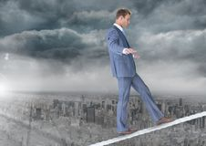 Walking businessman on tightrope over city and clouds. Digital composite of Walking businessman on tightrope over city and clouds Royalty Free Stock Images