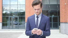 Walking Businessman Typing Text Message on Smartphone, Email, Outdoor. Creative designer , businessman stock video footage