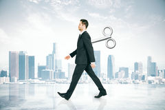 Walking businessman with wind-up key. Walking businessman with a wind-up key on his back walking on abstract city background. Concept of control Stock Photography