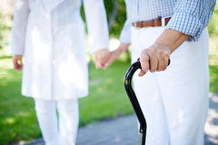 Walking with cane. Close-up of disabled female hand holding cane with her doctor walking near by royalty free stock images