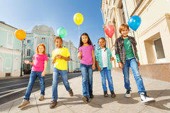 Walking children diversity with colorful balloons. Together in city centre in a row during summer time Stock Photos