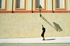 Walking in the city. Tourist walking in the old city at midday, long lamp shadow Royalty Free Stock Photography