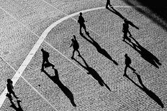 Walking in city space. Different people with shadows in a hurry Royalty Free Stock Images