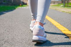 Walking. Close-up of women`s running shoes on a paved trail. Female feet in sneakers stock photo