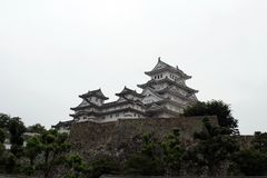 Walking closer to Himeji Castle that`s also called. `White Heron` located on a hilltop on a cloudy day. Pic was taken in August 2017 Royalty Free Stock Photography