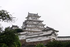 Walking closer to Himeji Castle that`s also called. `White Heron` located on a hilltop on a cloudy day. Pic was taken in August 2017 Stock Photo