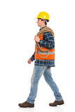 Walking construction worker with rope. Walking construction worker in yellow helmet and orange waistcoat with rope on his shoulder.  Full length studio shot Stock Photo