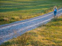 Walking in the country. Blond woman walking along a gravel-covered road in the country, photographed from the back royalty free stock photography