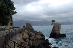 Walking couple along the sea. A couple walk along the rocky seaside in Portofino, Italy Royalty Free Stock Images