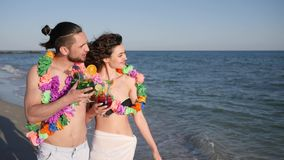 Walking couple in love, guy holding girl by hand, an exotic vacation, on background beach panorama, summer, slow motion, stock footage