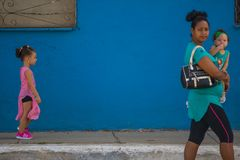 Walking Cuban people woman and daughter in street of Caribbean communism Cuba, America. Cuban people woman and children walking in colorful traditional street of royalty free stock image