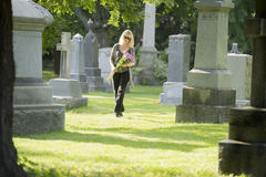 Walking Among the Dead. A woman walks through the cemetery with flowers stock photography