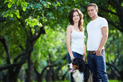 Walking the dog. Young couple walking with a dog in the park Stock Photos